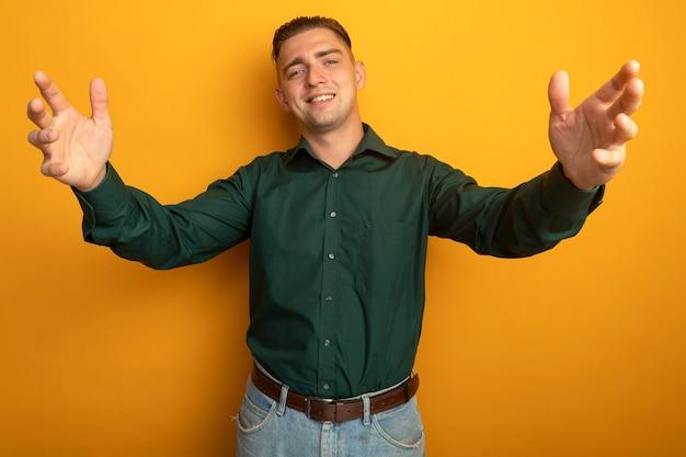 Hombre guapo joven en camisa verde sonriendo amable haciendo gesto de bienvenida amplia apertura de manos