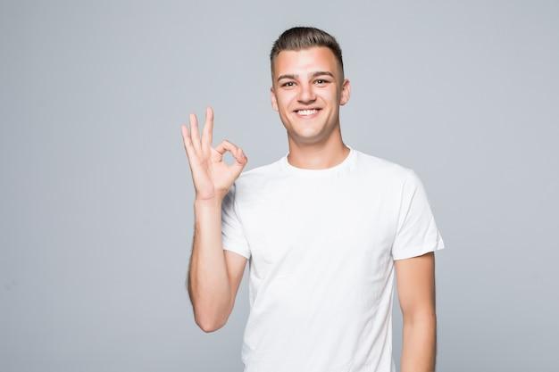 Hombre guapo joven en una camiseta blanca aislada en blanco muestra signo de ok