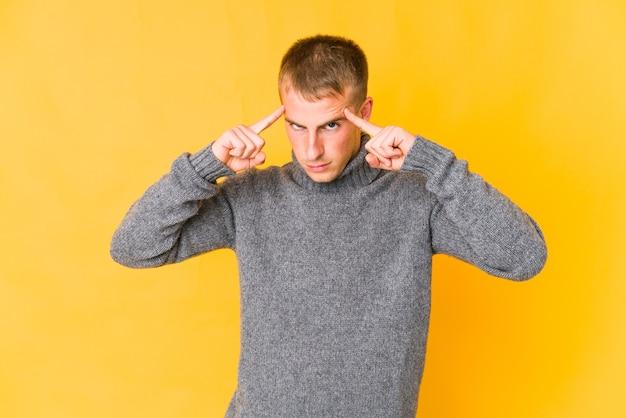 Hombre guapo joven se centró en una tarea, manteniendo los dedos índice apuntando la cabeza