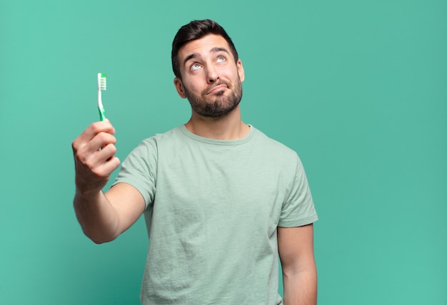 Hombre guapo joven con un cepillo de dientes.