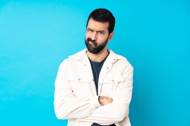 Hombre guapo joven con chaqueta de pana blanca sobre pared azul aislado sentirse molesto