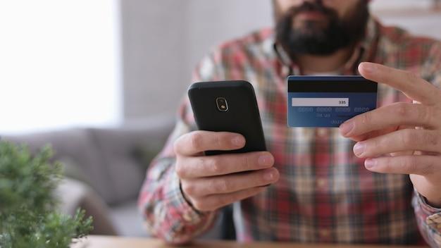 Hombre guapo joven de compras en línea con tarjeta de crédito, sentado en casa. servicio de aplicación de banca en línea.