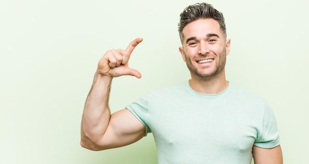 Hombre guapo joven contra una pared verde sosteniendo algo poco con los dedos índices, sonriente y confiado.