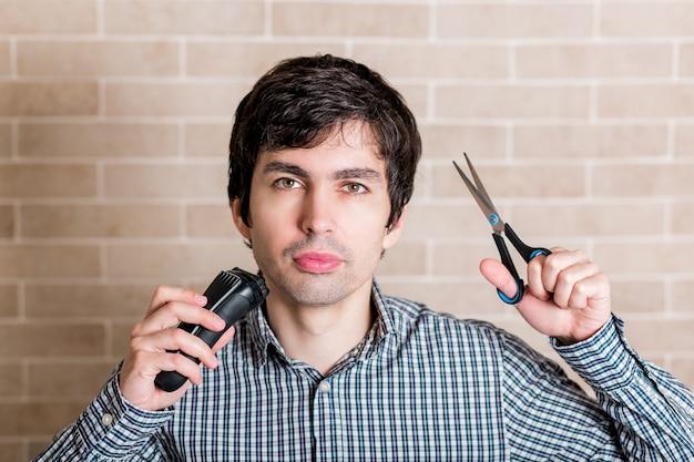Hombre guapo joven corta su propio cabello en casa.