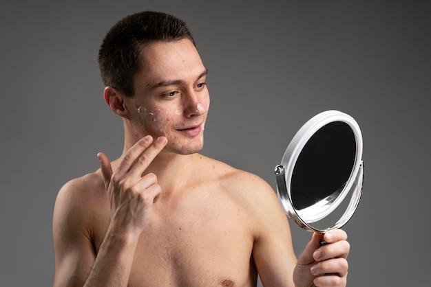Hombre guapo joven con una crema para el acné