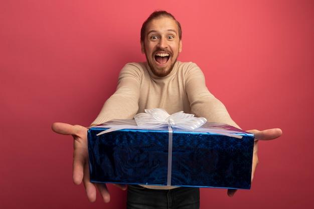 Hombre guapo joven en cuello alto beige mostrando caja de regalo loco feliz