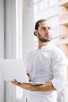 Hombre guapo joven con dispositivo portátil en la mano mirando lejos