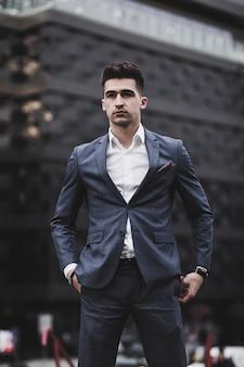 Hombre guapo joven elegante posando en traje de moda en la ciudad