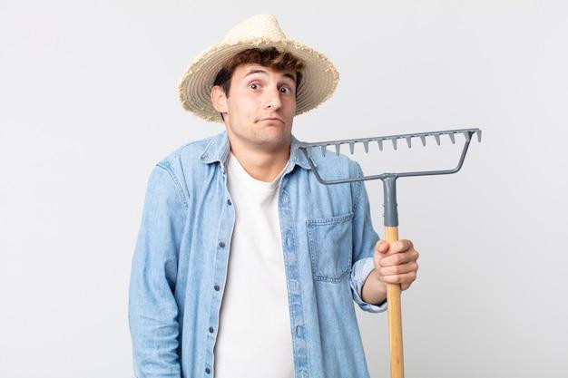 Hombre guapo joven encogiéndose de hombros, sintiéndose confuso e inseguro. concepto de granjero