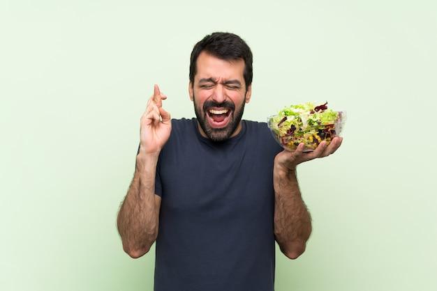 Hombre guapo joven con ensalada sobre pared verde aislada con cruzar los dedos