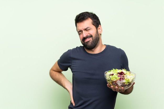 Hombre guapo joven con ensalada sobre pared verde aislado que sufre de dolor de espalda por haber hecho un esfuerzo