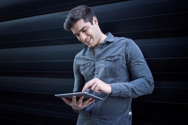 Hombre guapo joven escribiendo en su tableta