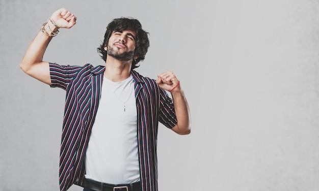 Hombre guapo joven escuchando música, bailando y divirtiéndose