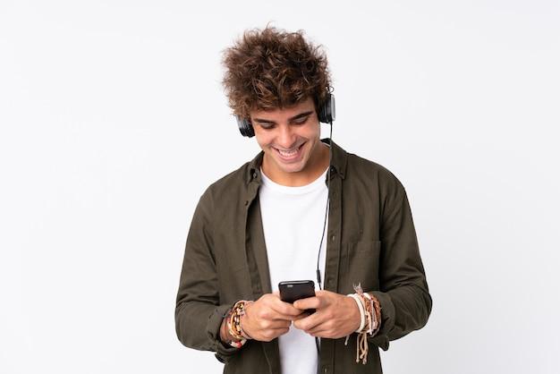 Hombre guapo joven escuchando música con un móvil sobre pared blanca aislada