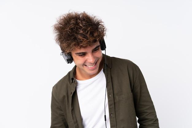 Hombre guapo joven escuchando música sobre pared blanca aislada