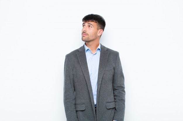 Hombre guapo joven con una expresión preocupada, confundida y despistada, mirando hacia arriba para copiar espacio, dudando sobre la pared blanca