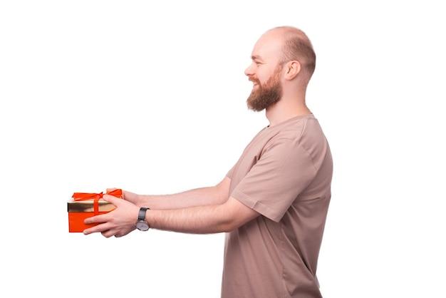 Hombre guapo joven feliz dando una caja de regalo en blanco