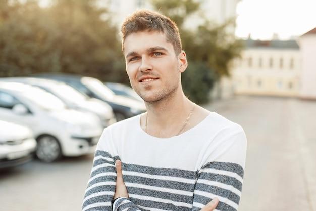 Hombre guapo joven feliz de pie en el estacionamiento al atardecer
