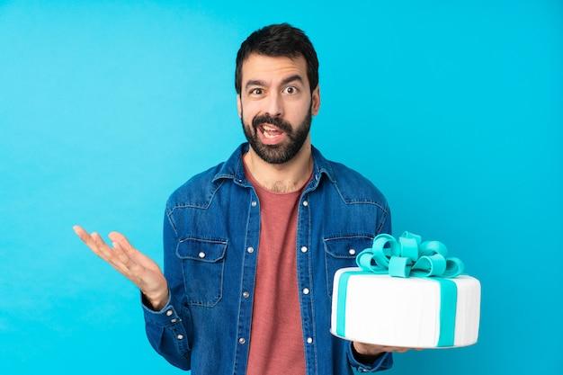 Hombre guapo joven con un gran pastel sobre la pared azul aislada haciendo gesto de dudas
