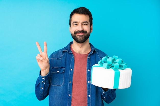 Hombre guapo joven con un gran pastel sobre la pared azul aislada que muestra el signo de la victoria con ambas manos