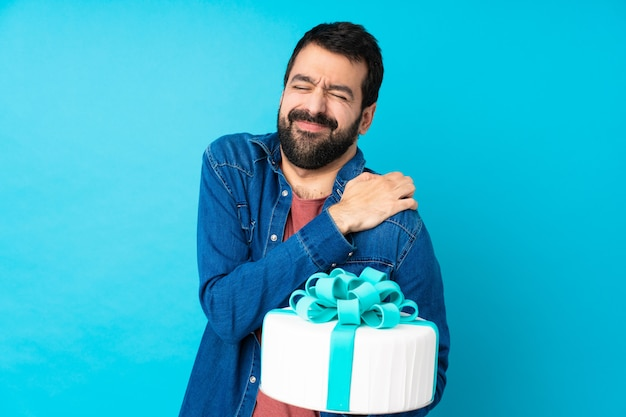 Hombre guapo joven con un gran pastel sobre la pared azul aislada que sufre de dolor en el hombro por haber hecho un esfuerzo