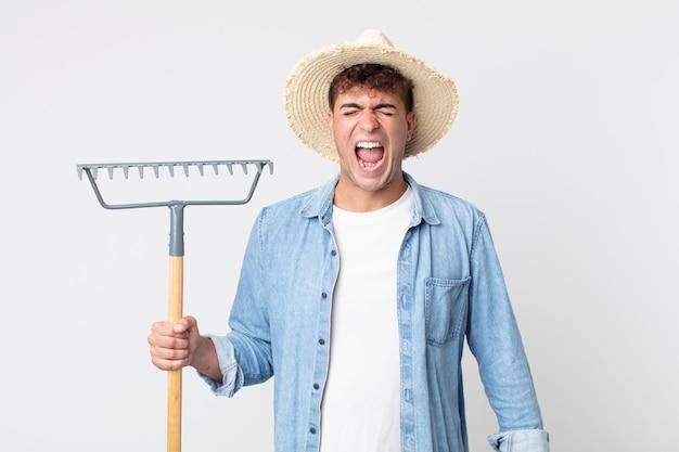Hombre guapo joven gritando agresivamente, luciendo muy enojado. concepto de granjero