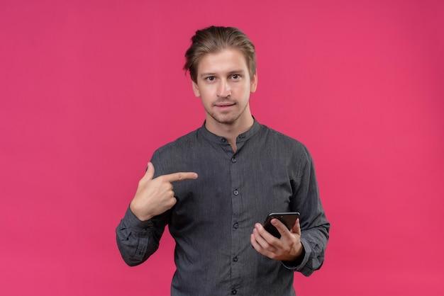 Hombre guapo joven hlding teléfono móvil apuntando a sí mismo