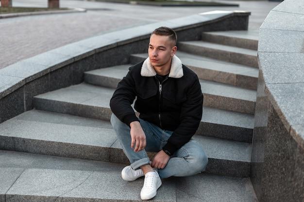 Hombre guapo joven en jeans azul con una chaqueta negra en zapatillas blancas con un peinado sentado en una escalera de piedra vintage en la ciudad