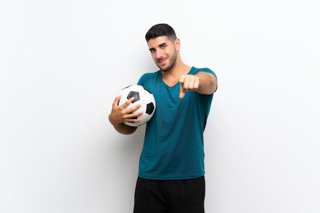 Hombre guapo joven jugador de fútbol sobre pared blanca