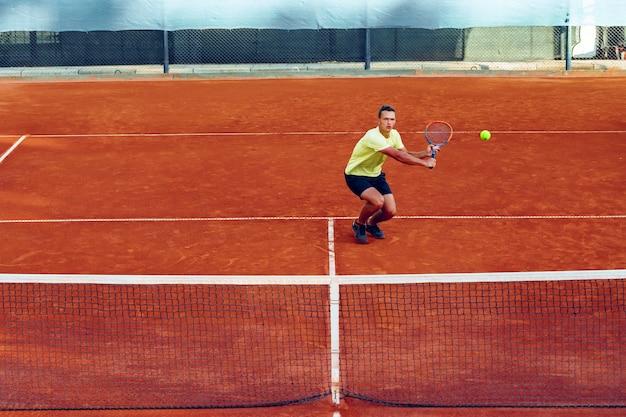 Hombre guapo joven jugando al tenis en la cancha de tenis de arcilla