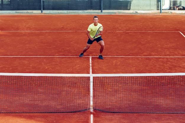 Hombre guapo joven jugando al tenis en la cancha de tenis