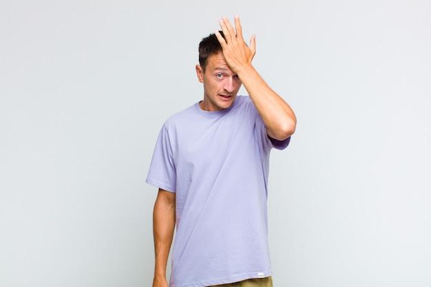 Hombre guapo joven levantando la palma de la mano a la frente pensando ¡uy, después de cometer un error estúpido o recordar, sentirse tonto!