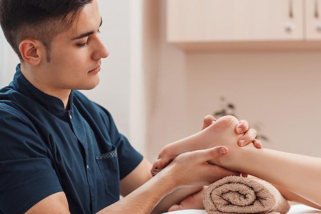 Hombre guapo joven masajeando el pie femenino desnudo