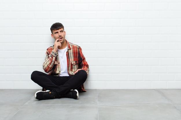 Hombre guapo joven con mirada sorprendida, nerviosa, preocupada o asustada, mirando hacia el lado hacia el espacio de copia sentado en el piso de cemento