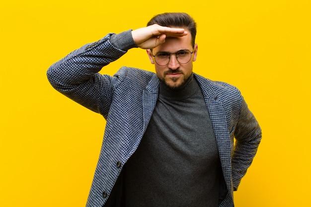 Hombre guapo joven mirando desconcertado y asombrado, con la mano sobre la frente mirando a lo lejos, mirando o buscando contra la pared naranja