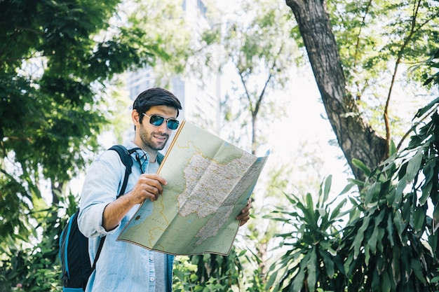 Hombre guapo joven mirando un mapa de papel y usando gafas de sol en un parque público con una cara feliz de pie y sonriendo