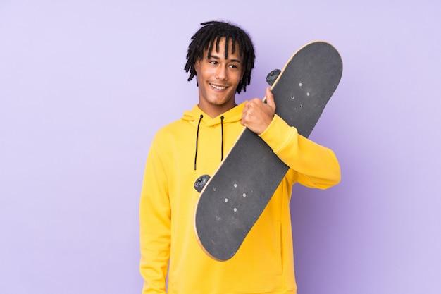 Hombre guapo joven patinador sobre pared aislada con expresión feliz