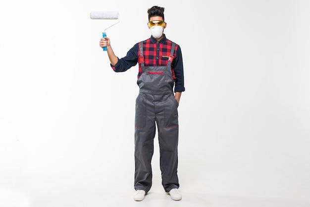 Hombre guapo joven pintor con rodillo vistiendo uniforme sobre espacio en blanco aislado con una cara feliz de pie y sonriente
