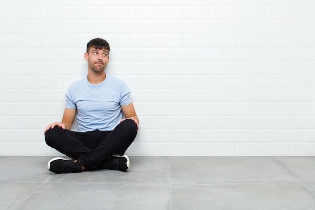 Hombre guapo joven preguntándose, pensando pensamientos e ideas felices, soñando despierto, mirando para copiar espacio en el lado sentado en el piso de cemento