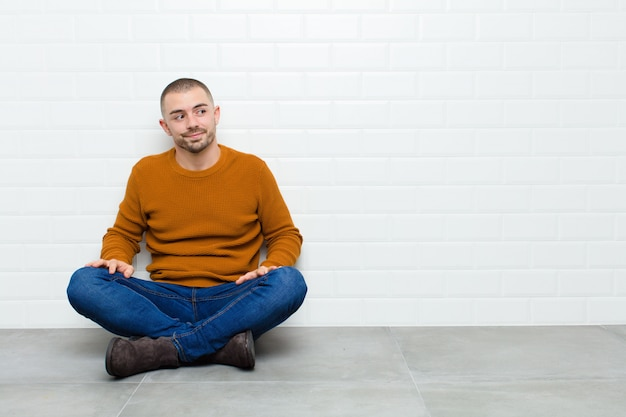 Hombre guapo joven preguntándose, pensando pensamientos e ideas felices, soñando despierto, mirando de lado sentado en el suelo