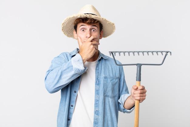 Hombre guapo joven que cubre la boca con las manos con una sorpresa. concepto de granjero