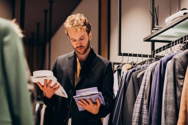 Hombre guapo joven que elige la camisa en una tienda