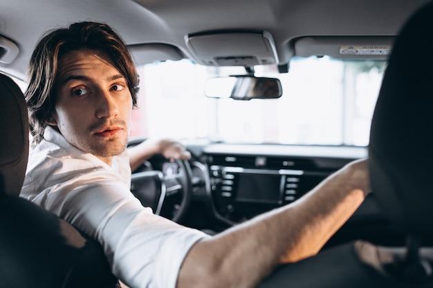 Hombre guapo joven que elige un coche en una sala de exposición de automóviles