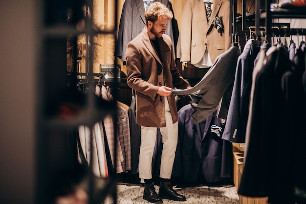 Hombre guapo joven que elige la ropa en la tienda
