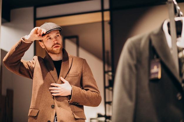 Hombre guapo joven que elige el sombrero en la tienda