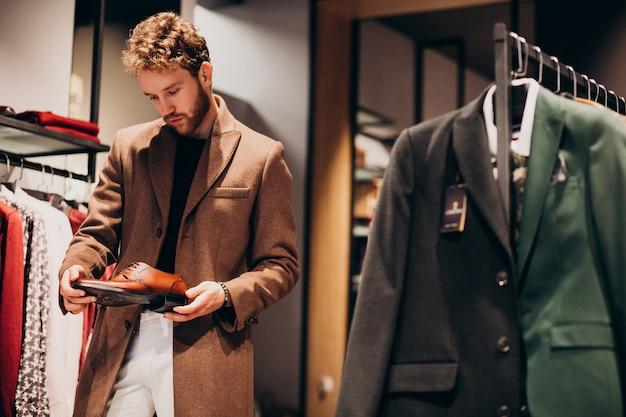 Hombre guapo joven que elige los zapatos en una tienda