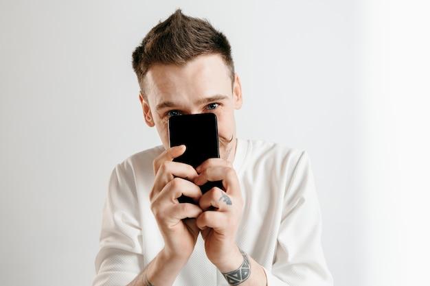 Hombre guapo joven que muestra la pantalla del teléfono inteligente aislado en gris walll en estado de shock con una cara de sorpresa