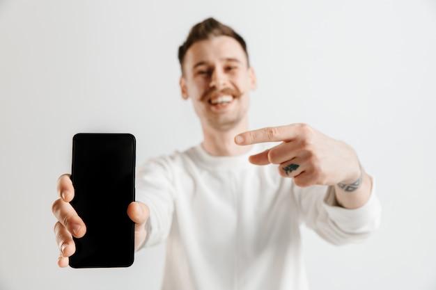 Hombre guapo joven que muestra la pantalla del teléfono inteligente en gris con una cara de sorpresa.