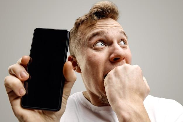 Hombre guapo joven que muestra la pantalla del teléfono inteligente sobre fondo gris con una cara de sorpresa. las emociones humanas, el concepto de expresión facial.