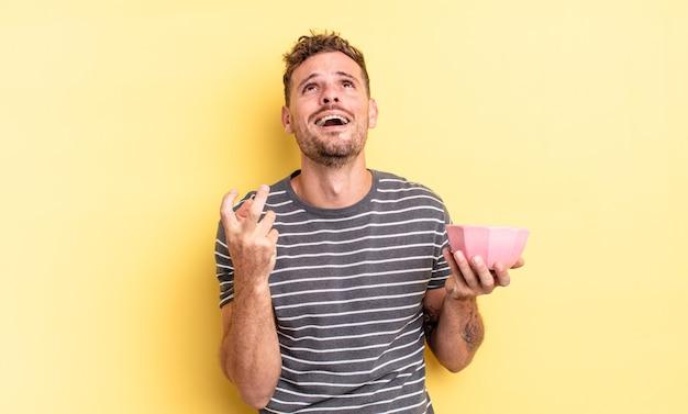 Hombre guapo joven que parece desesperado, frustrado y estresado concepto de tazón vacío